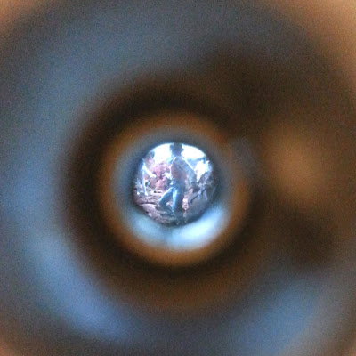 Tiny miniature cowboy figure, seen through a peep hole.