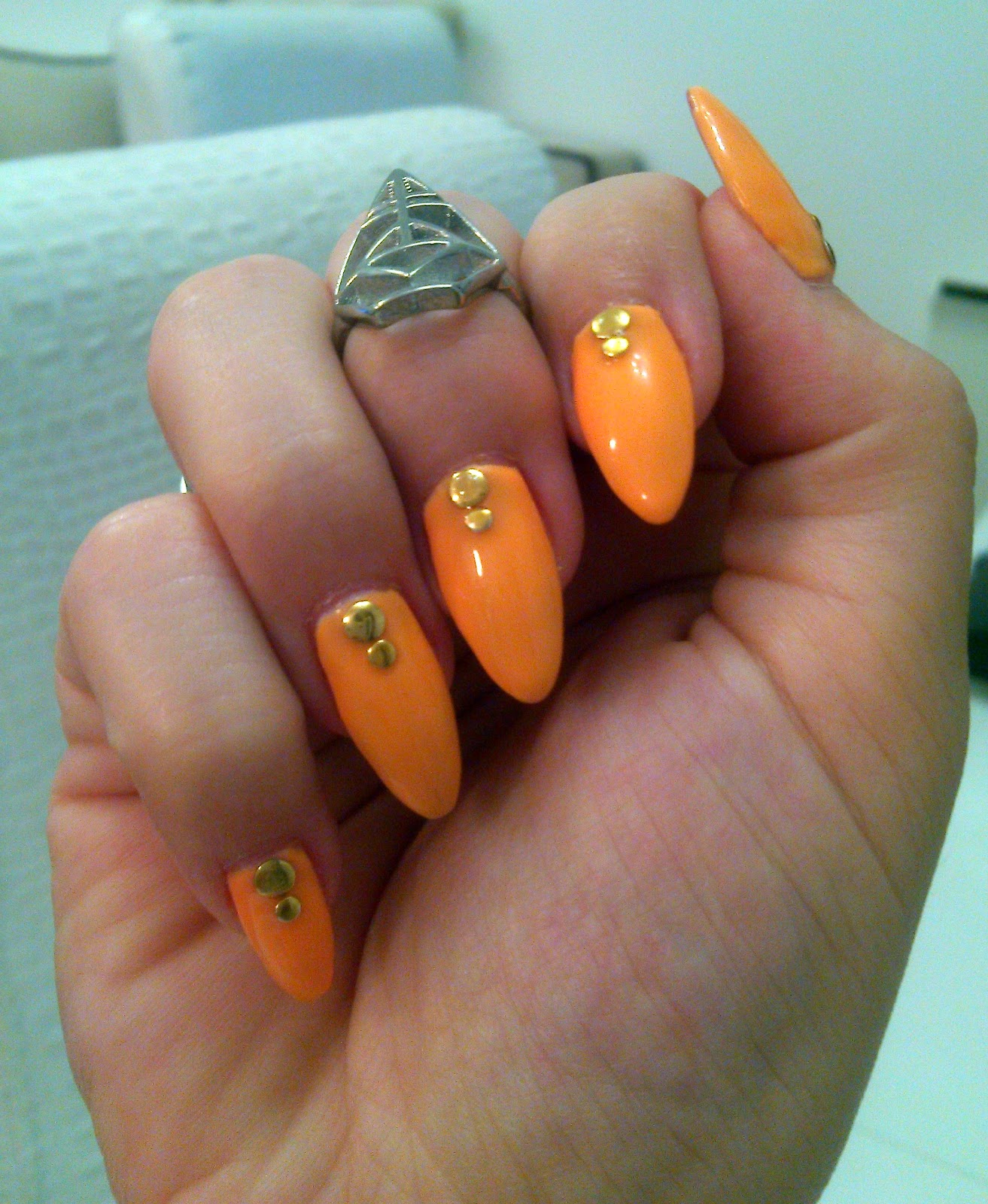 neon orange stiletto nails with round studs,