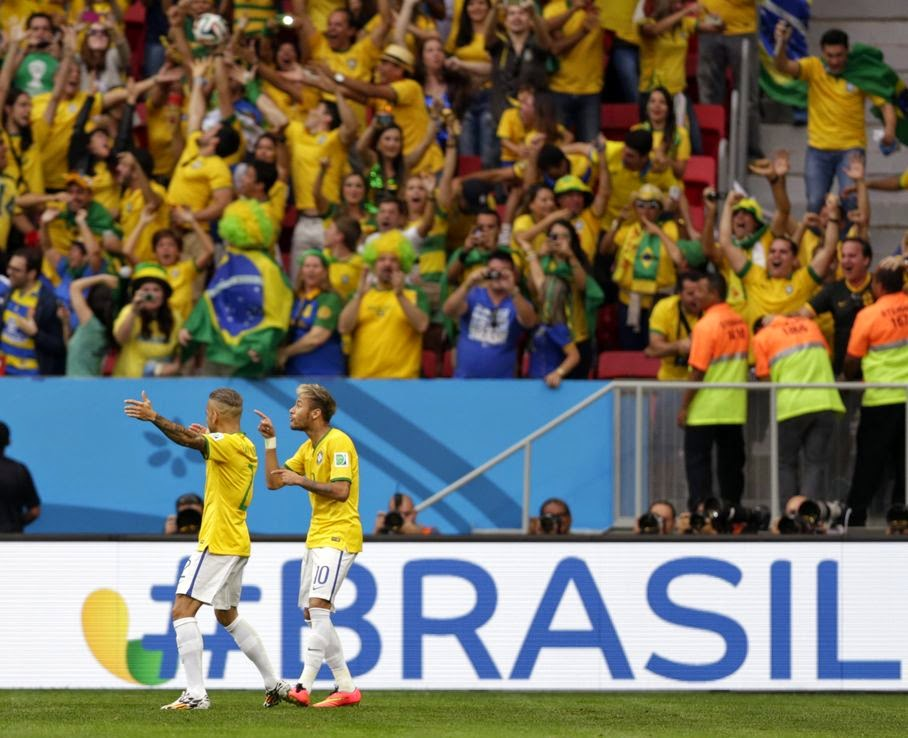 Brazil's Neymar, second left, celebrates scoring the opening goal during the group A World Cup soccer match between Cameroon and Brazil at the Estadio Nacional in Brasilia, Brazil, Monday, June 23, 2014.