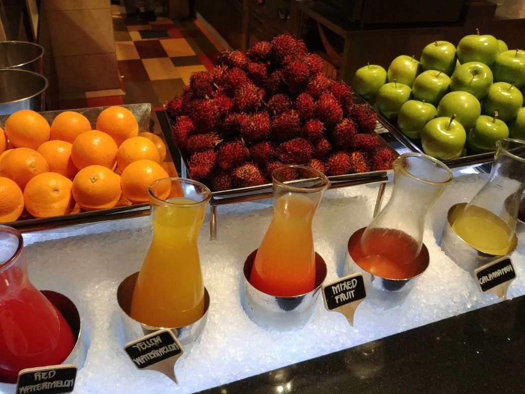 Fresh orange, rambutan, green apples, and fruit juices at the dessert station of The Grand Kitchen