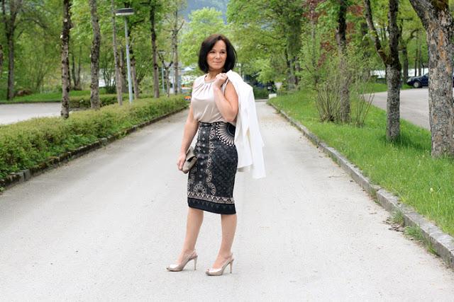 Женщина за 50 в белом топе и юбке с принтом, прикрывающей колено