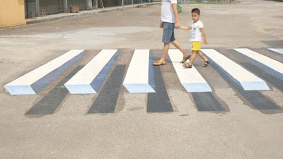 mother and daughter walking across the street on 3D crosswalk