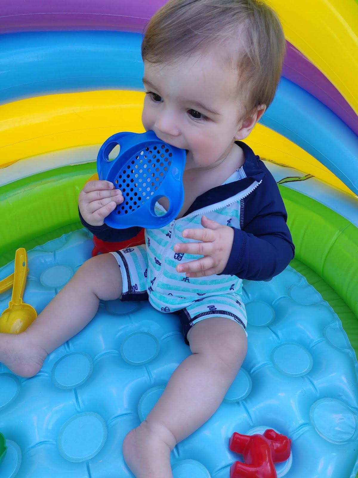 baby playing in paddling pool