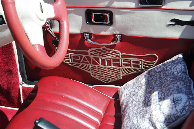 a red leather car interior embroidered with 'panther' and emblem in cream