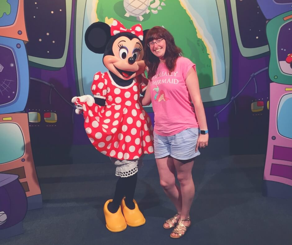 Morgan Prince stands next to Minnie Mouse, she has her arm around her waist. Both are smiling and looking at the camera.