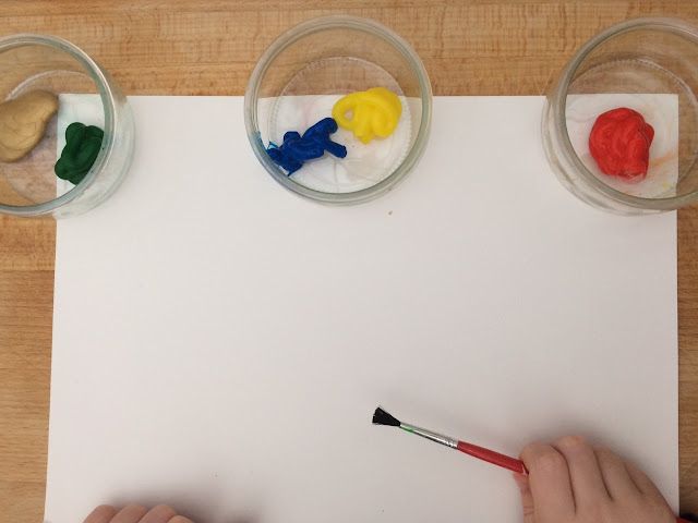 Paint in pots, a piece of card and a paint brush, with a child's hand ready to paint