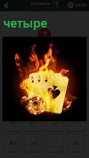 В огне пылают четыре карты разной масти с игральной фишкой для казино, символизирующие проигрыш в игре
