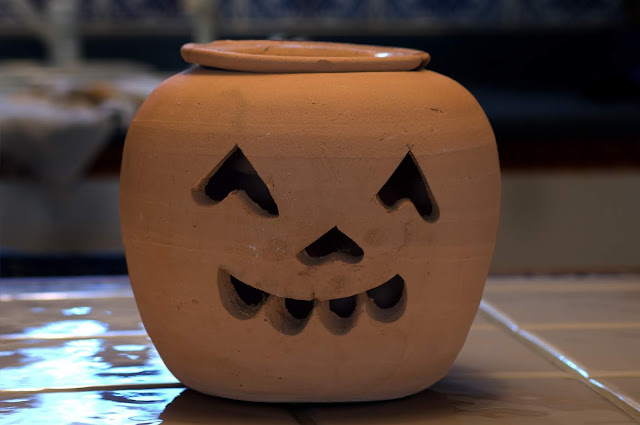 A large clay jack-o-lantern pot which could easily be used for holding wrapped goodies, or a lit candle.