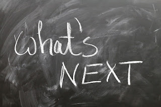 "A chalkboard, with ""what's next"" written on it in white chalk"