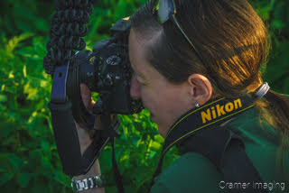 Photo of professional landscape photographer Audrey with camera in hand taking a picture by Cramer Imaging
