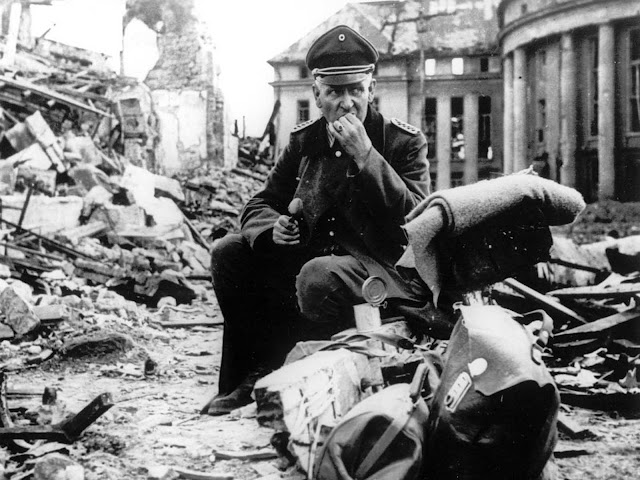 A German officer eats C-rations as he sits amid the ruins of Saarbrücken, a German city and stronghold along the Siegfried Line, in early spring of 1945.