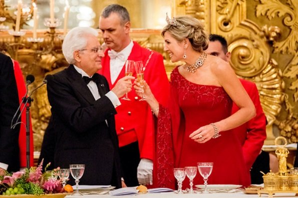 Queen Maxima at gala dinner wore a red gown by Valentino. Queen Maxima wear diamond tiara. diamond earrings. Mrs Laura Mattarella