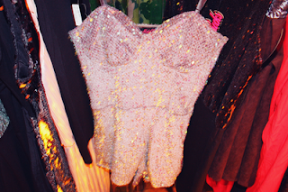 shot of a sequined playsuit by motelrocks on a hanger in front of some of their range