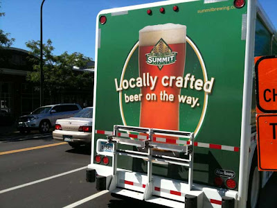 Back of truck with glass of beer and words Locally Crafted Beer on the Way