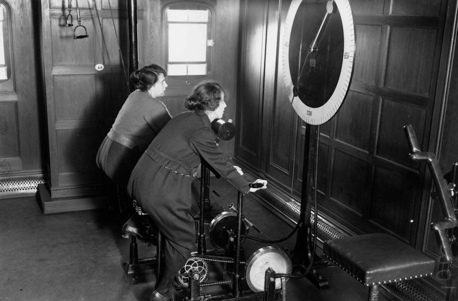 Two women using the cycle machine in the gym on board the Homeric Liner, taken over from the Germans by White Star. 1922.