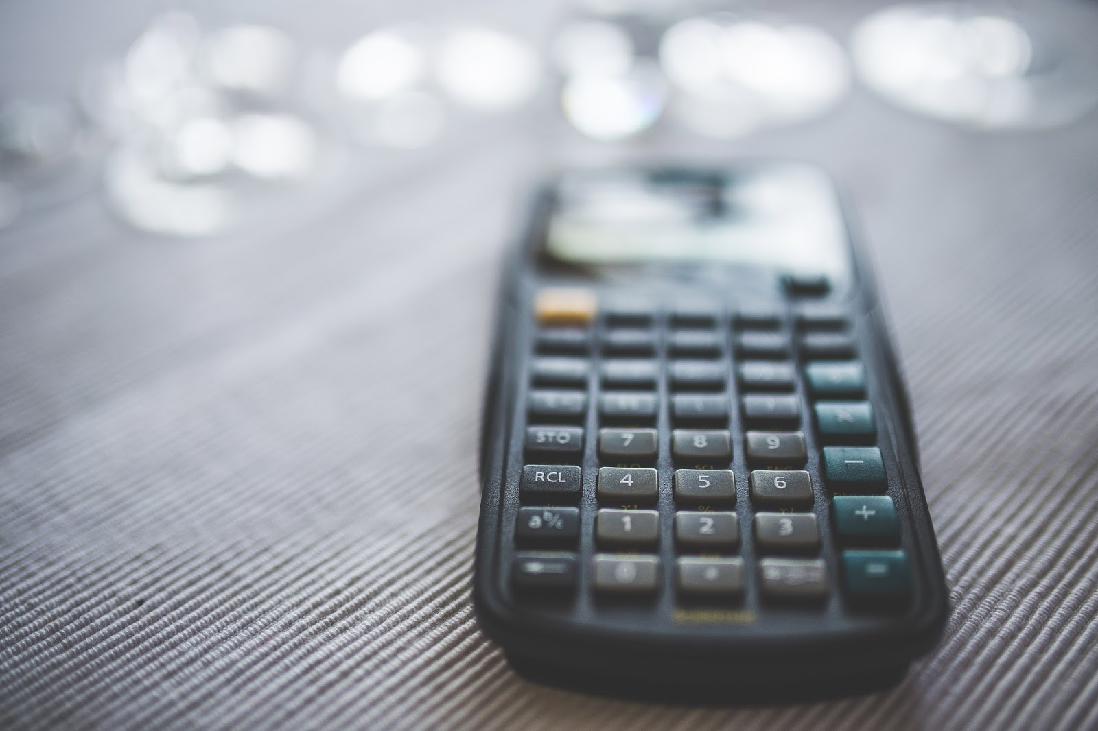Calculator on a table with coins blurred in the distance