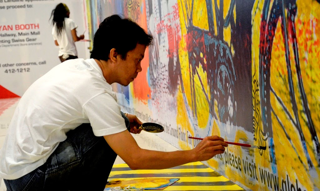 - Artist Herald GuarinCorpuz working on his piece for the Globe GEN3 stores