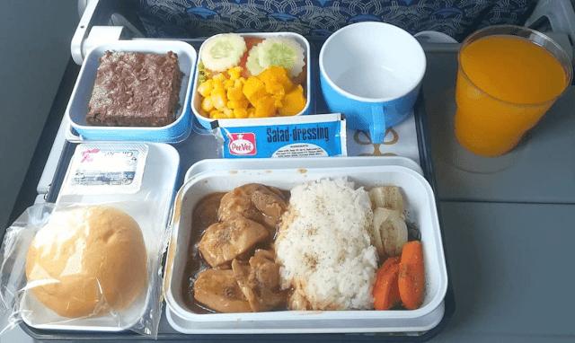 Hãng hàng không Ai Cập phục vụ cơm gà, rau củ, salad kèm sốt, một phần bánh brownie socola và một miếng bánh mì cùng với một cốc nước cam.