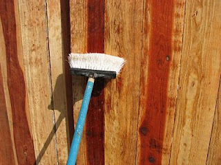 Using a plastic broom to spread solution around and work it into the wood grain.