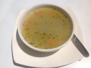 zu sehen ist eine  weiße Suppentasse mit einer Brühe auf einer Untertasse
