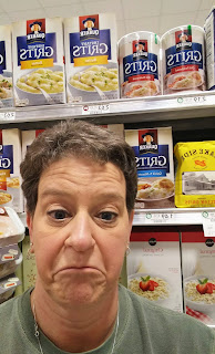 woman in front of grits at the grocery store with a not-so-sure look on her face
