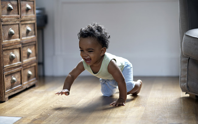 Happy baby crawls on a clean wood floor.