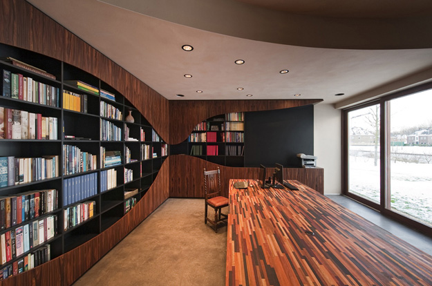 Photo of large home library with wooden walls and table