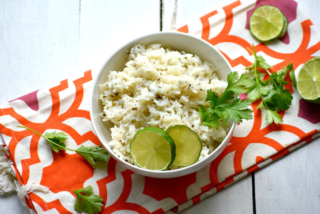 Cilantro lime rice in a bowl on a towel with limes and cilantro