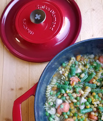 enameled dutch oven with pasta and veggies in it
