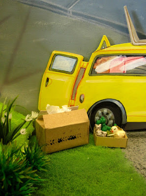 One-twelfth scale miniature scene of a yellow Mini van in a garden. It's back doors are open with two cardboard cartons on the ground next to it.