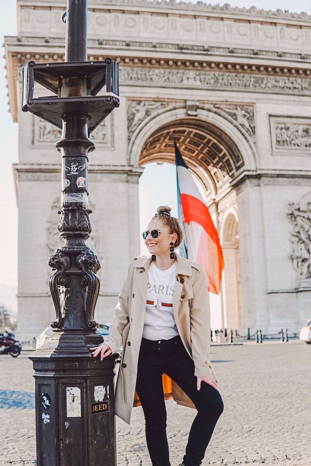 amanda burrows standing in front of the arc de triomphe paris france wearing a tan trench coat from h&m in europe