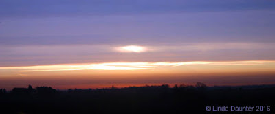 a view of a sunrise with streak of light showing through dark clouds