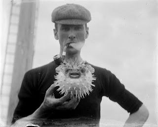 man holding puffer fish puffing on a pipe