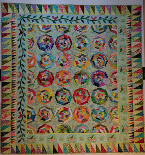 Scrap spiderweb quilt with light blue background has appliqued and pieced borders