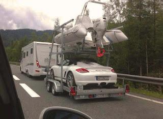 Ett tyskregistrerat ekipage verkar vara ute på de svenska vägarna. Motorbåt och Porsche på släpkärran till husbilen..