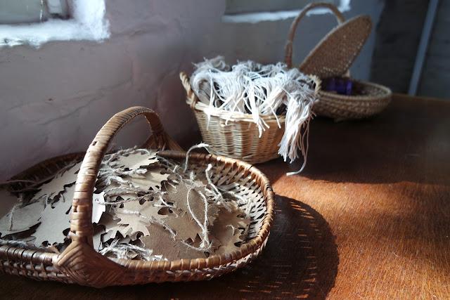 a wicker basket of brown leaf shaped cards, and another filled with paper labels, on a wooden table