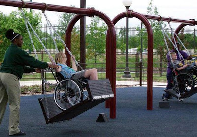 A child in a wheelchair enjoys using a wheelchair friendly swing at a play park.