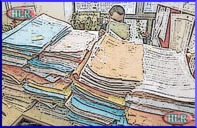 Imagen de la mesa del auxiliar administrativo llena de expedientes