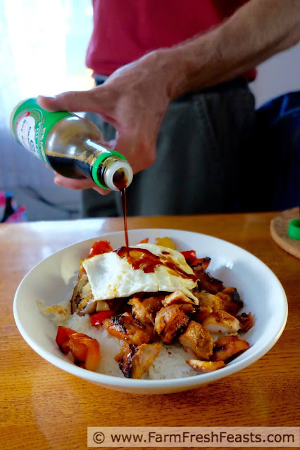 a handsome man pouring soy sauce onto a fried egg atop a Korean-seasoned grilled chicken, eggplant, and pepper rice bowl