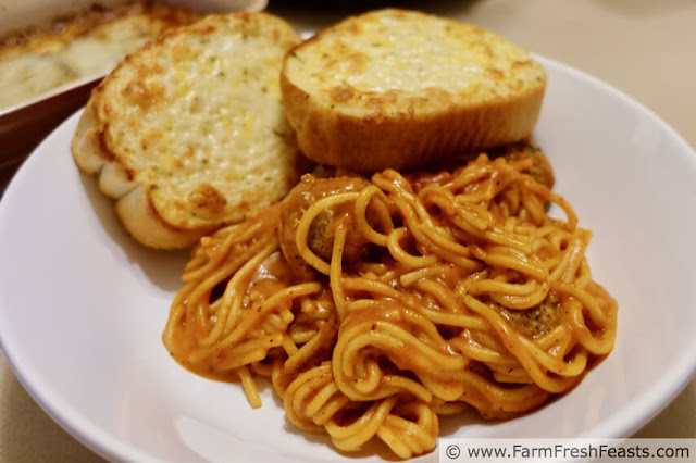 image of a shallow pasta bowl with pressure cooked spaghetti and meatballs and a side of garlic bread
