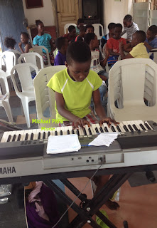nigerian small boy playing agidigba oo on the piano
