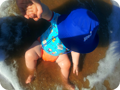 baby sat in the sea, baby enjoying the beach