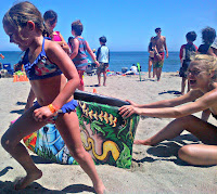"A camper plays the ""Jumping over the Boogie Board"" games her counselor holds the boogie boards"