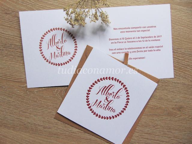 Invitación de boda doblada de estilo moderna e informal con corona de hojas y nombre de los novios en estilográfica