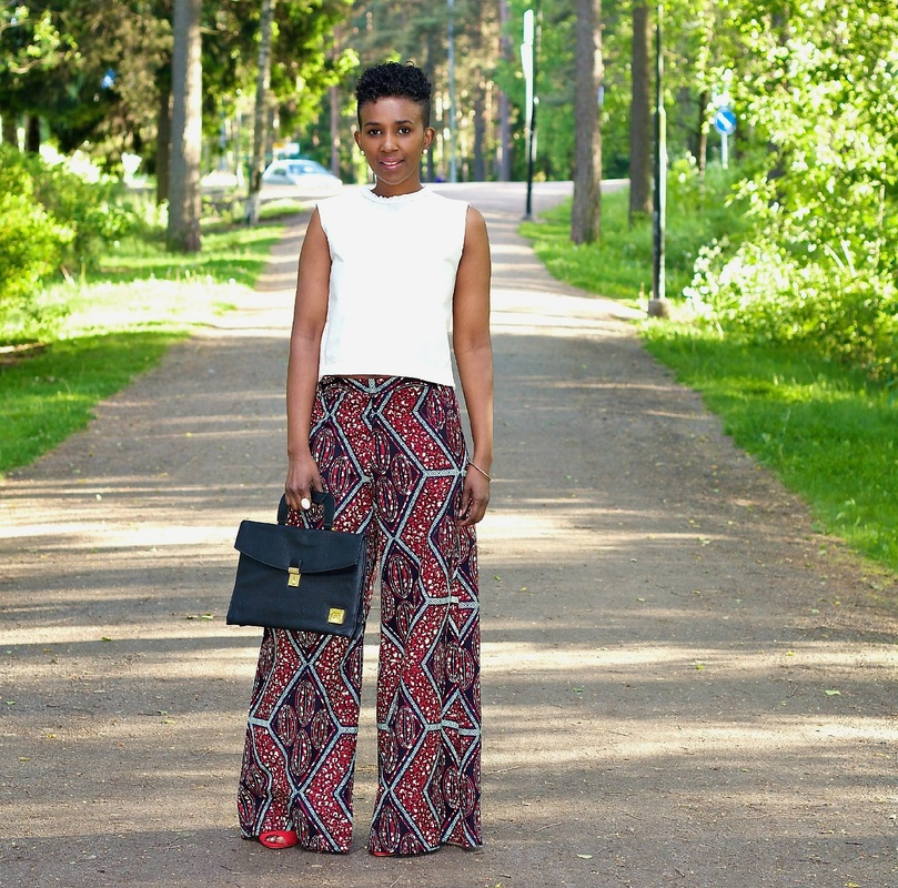 woman in white top and african print palazzo pants standing on the street