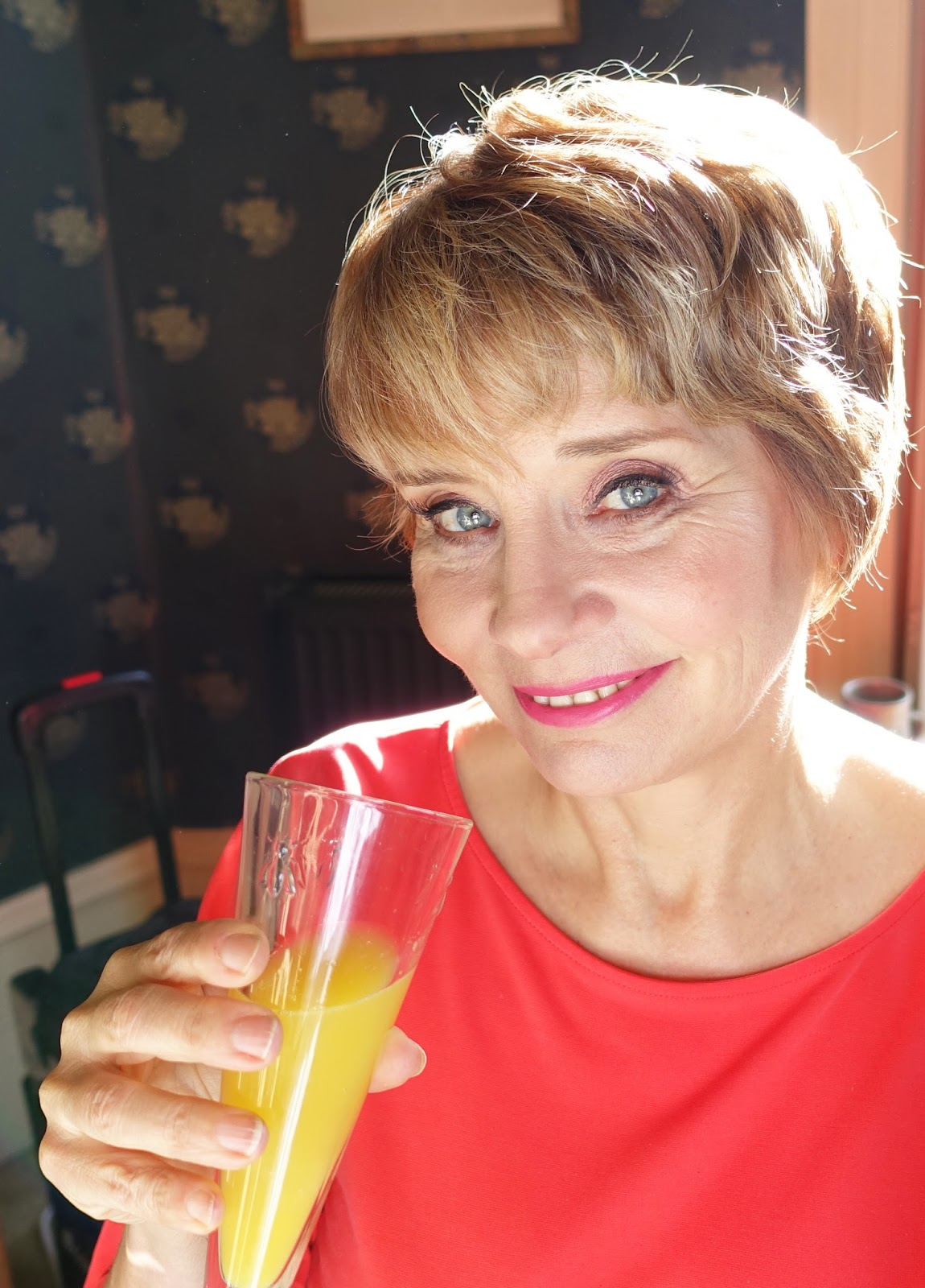 Image showing a woman sipping a glass of Bucks Fizz