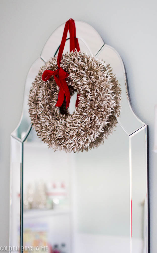 Glitter wreath on venetian arch mirror with bevels in master bathroom with Christmas decor