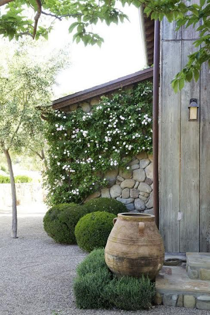 outdoor garden with wooden home, boxwood, gravel and potery