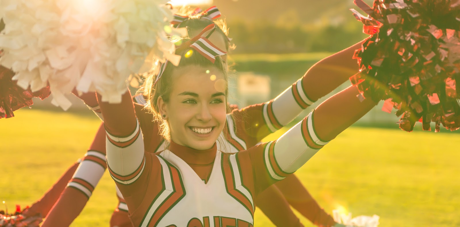Smiling cheerleader with poms.