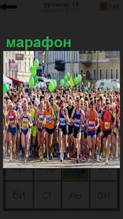 По улицам города бегут марафон большое количество людей и спортсменов
